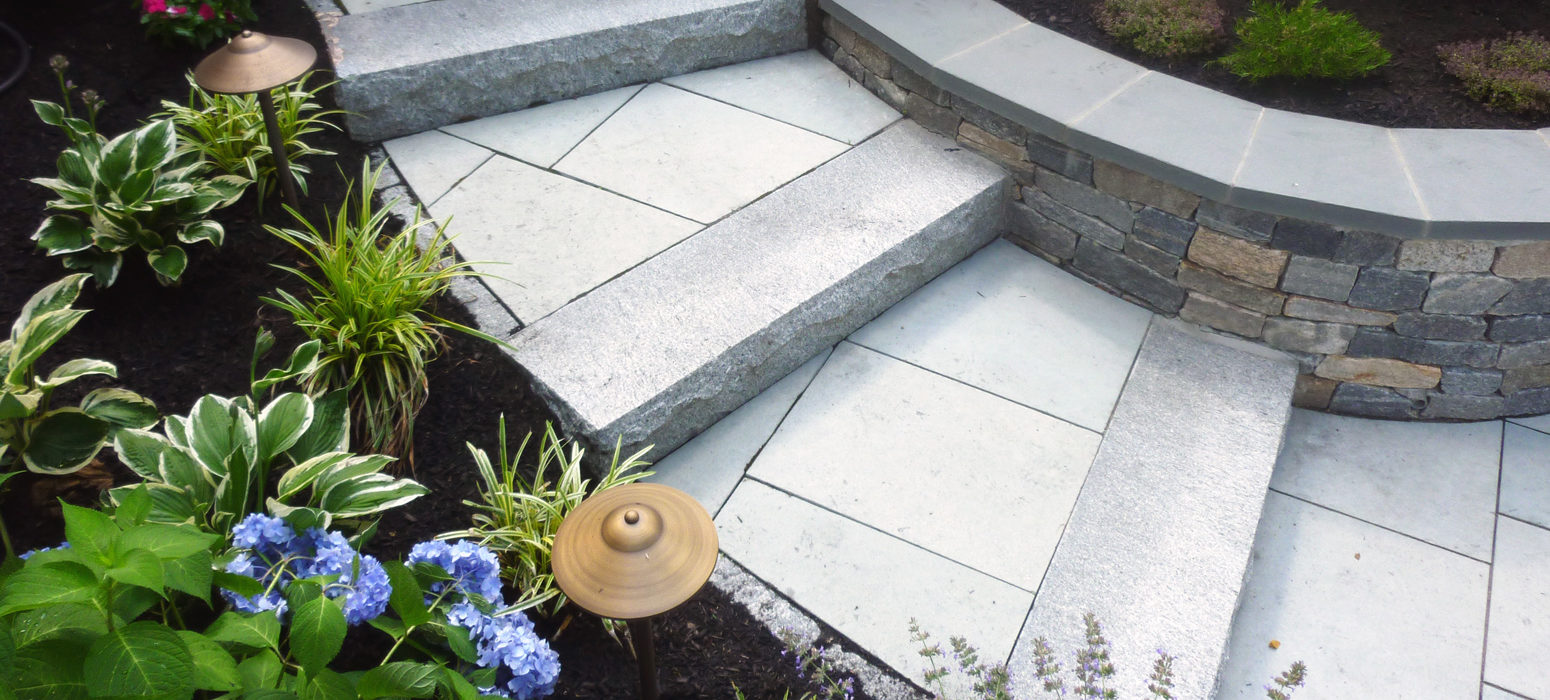 Curved Granite steps and natural stone wall landscaping